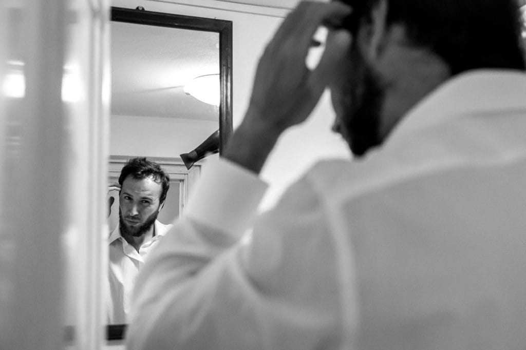sposo allo specchio durante la preparazione del matrimonio in sicilia