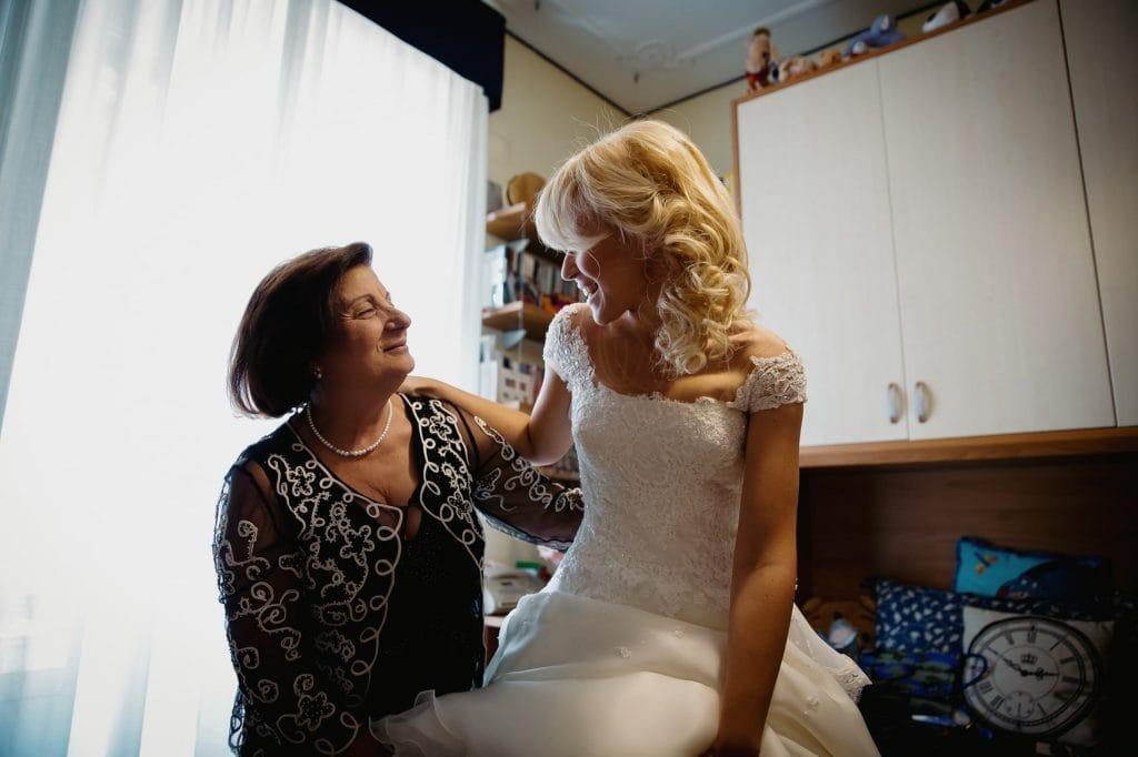 mamma della sposa aiuta la sposa a vestirsi