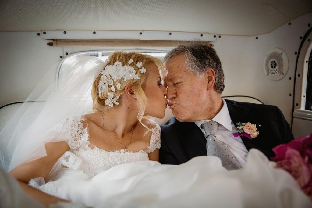 fotografo matrimonio villa miani bacio tra la sposa e il papˆ in auto
