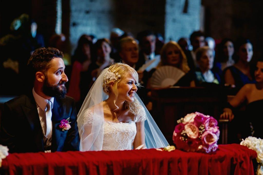 sposi in chiesa seduti davanti all'altare fotografati dal fotografo matrimoni villa miani