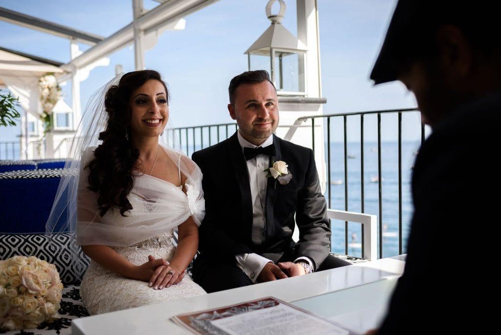 sposi davanti al celebrante durante il matrimonio intimo al rada di positano