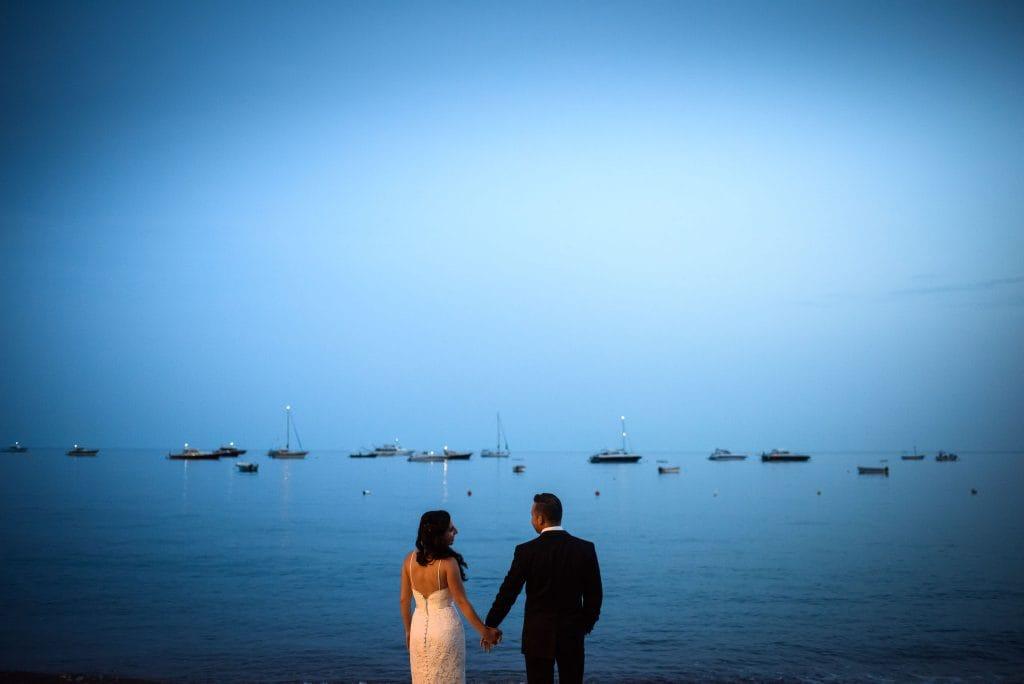 gli sposi si tengono per mano di fronte al mare di positano