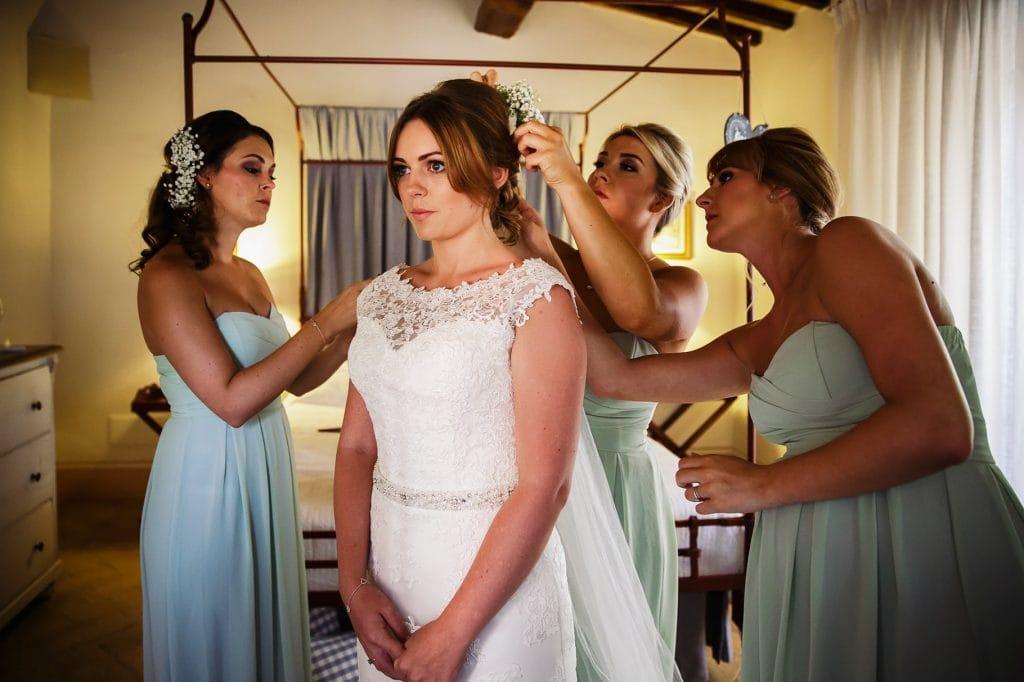 la sposa indossa il vestito e le damigelle lÕaiutano a mettere il velo