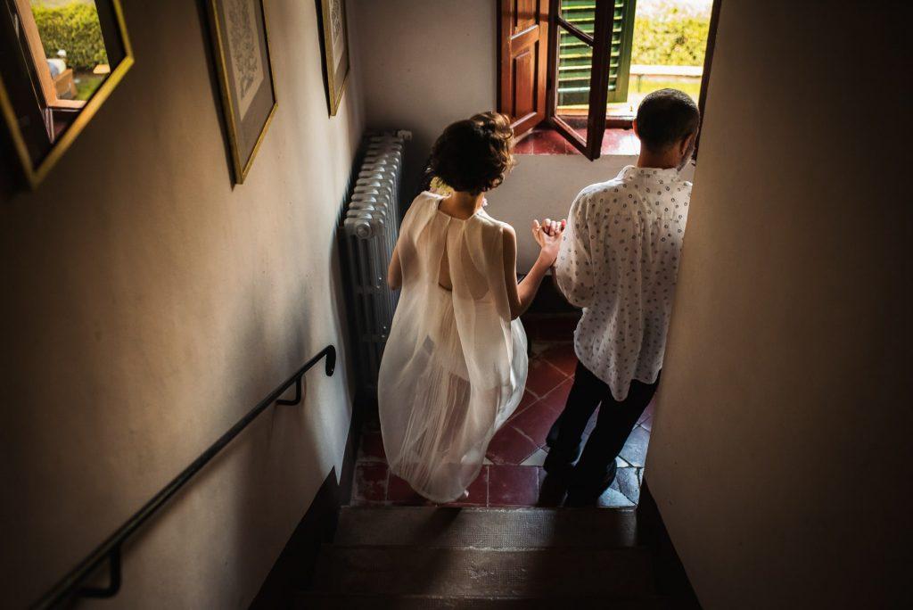 la sposa con il padre scende le scale per recarsi alla cerimonia di matrimonio in toscana