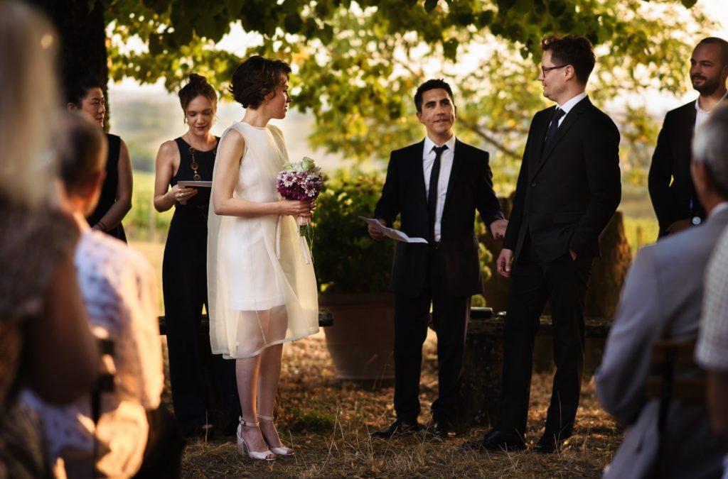 gli sposi con il celebrante durante la cerimonia di matrimonio all'aperto in toscana