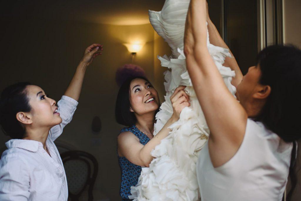 sposa prende il vestito aiutata dalle testimoni