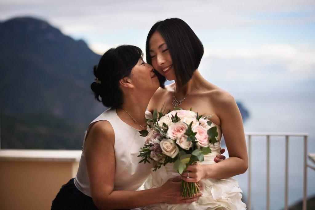 sposa con abito e bouquet bacia la mamma