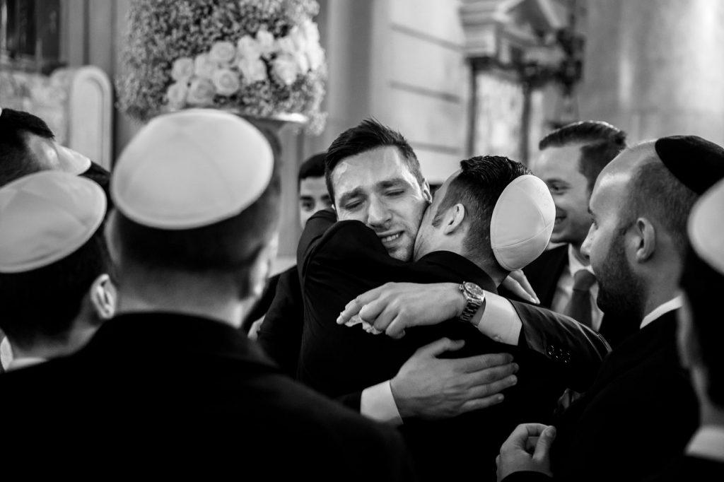 sposo abbraccia un amico dopo la cerimonia in sinagoga