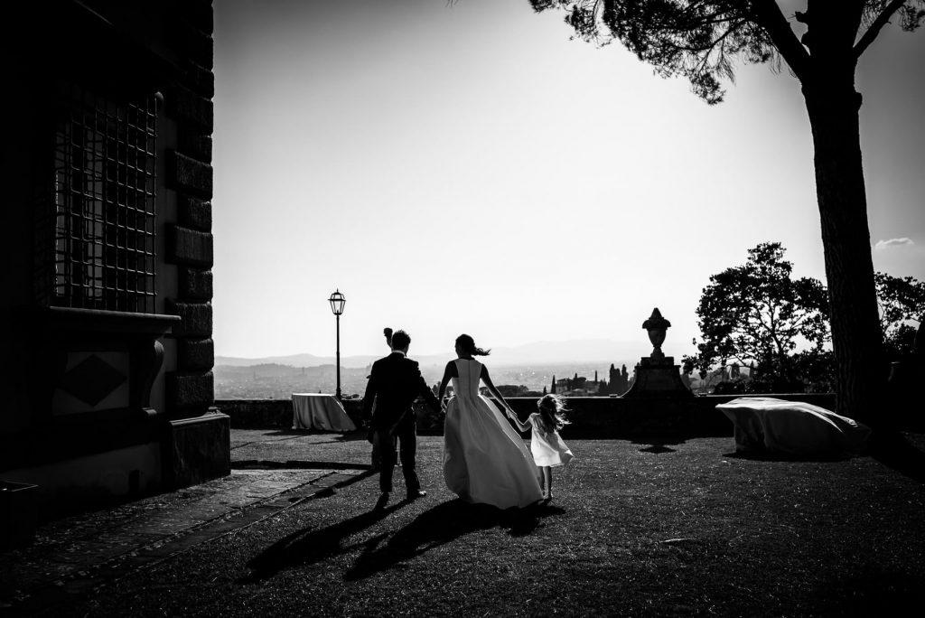 gli sposi di spalle con una bambina a villa gamberaia