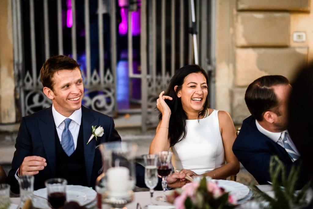 gli sposi ridono al tavolo di nozze