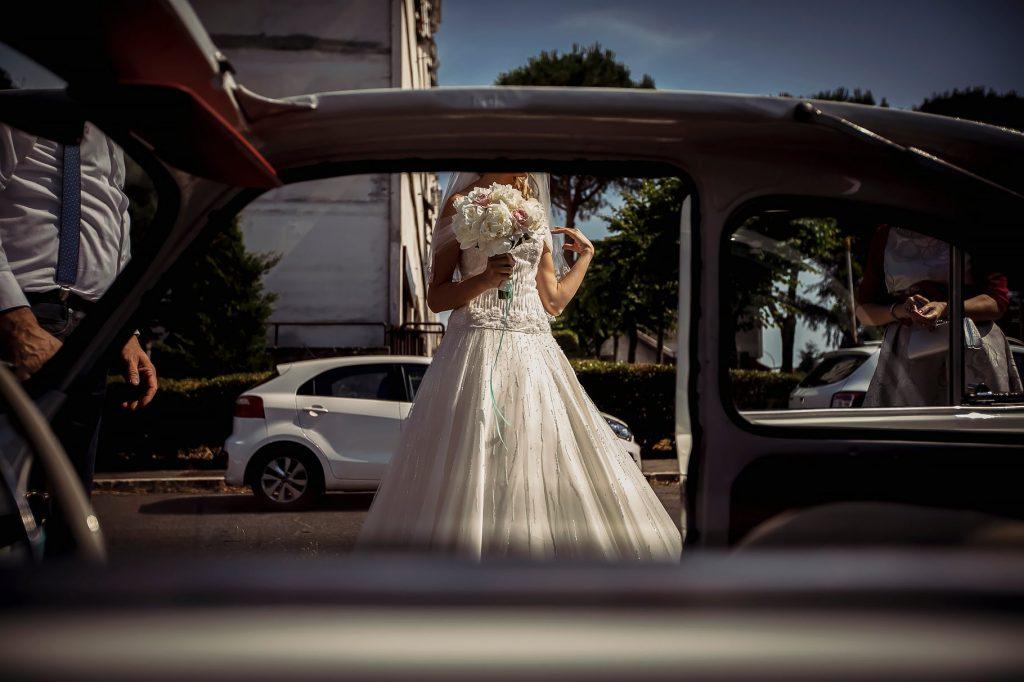 uscita di casa della sposa che entra in macchina per andare al matrimonio estivo a roma