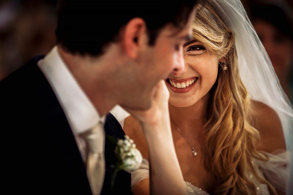 sposa sorridente accarezza sposo al matrimonio a roma