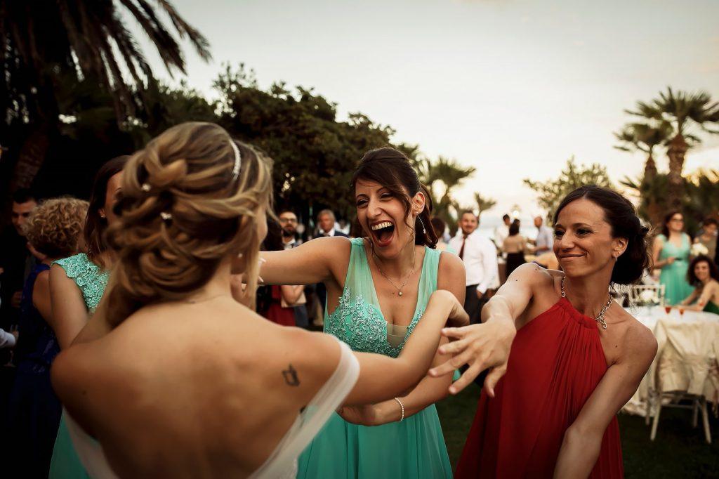 amiche della sposa che ballano e si divertono al ricevimento di un matrimonio estivo a roma