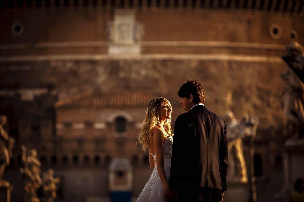 la sposa e lo sposo sul ponte dellÕangelo con il castel santÕangelo a roma