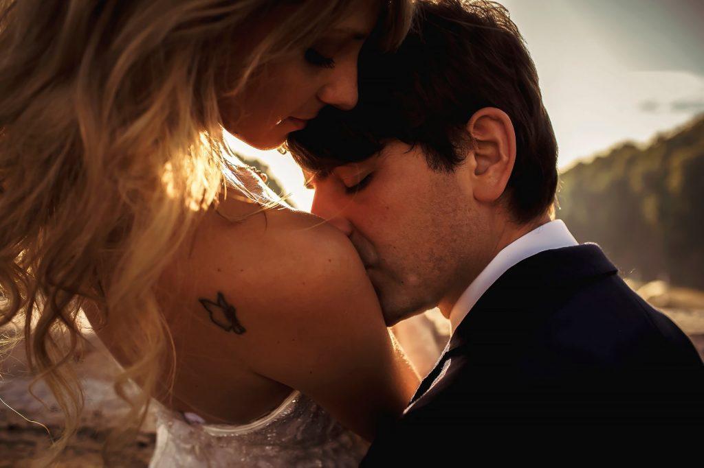 sposo che bacia la spalla della sposa con tatuaggio a roma