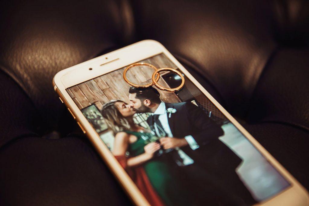 dettaglio delle fedi con foto di coppia che si bacia