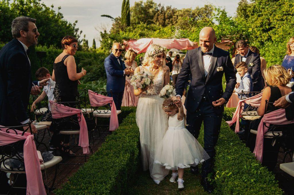 uscita degli sposi dalla cerimonia del matrimonio allÕaperto a villa rosantica