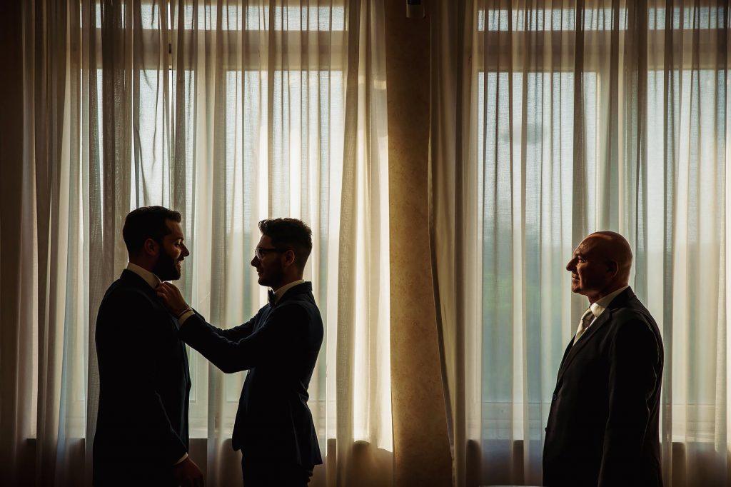 lo sposo si veste aiutato dal testimone e dal padre