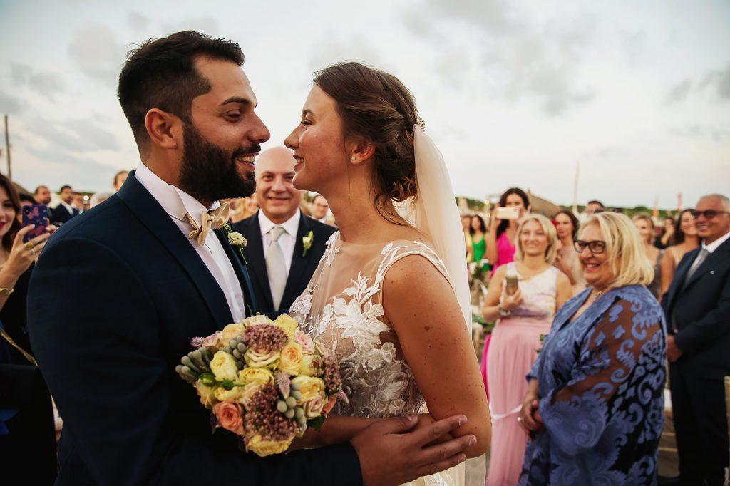 gli sposi si incontrano alla cerimonia del matrimonio in spiaggia