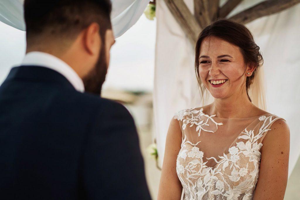 scambio delle promesse di matrimonio, la sposa guarda lo sposo e sorride