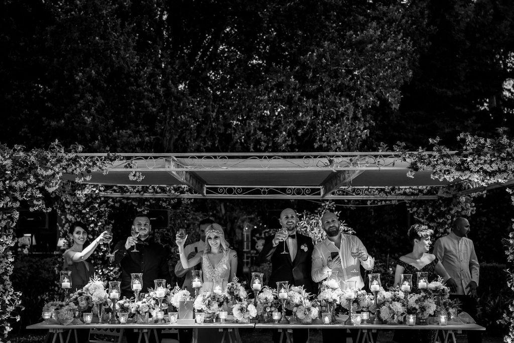 sposi e testimoni brindano al tavolo di nozze al matrimonio allÕaperto a villa rosantica