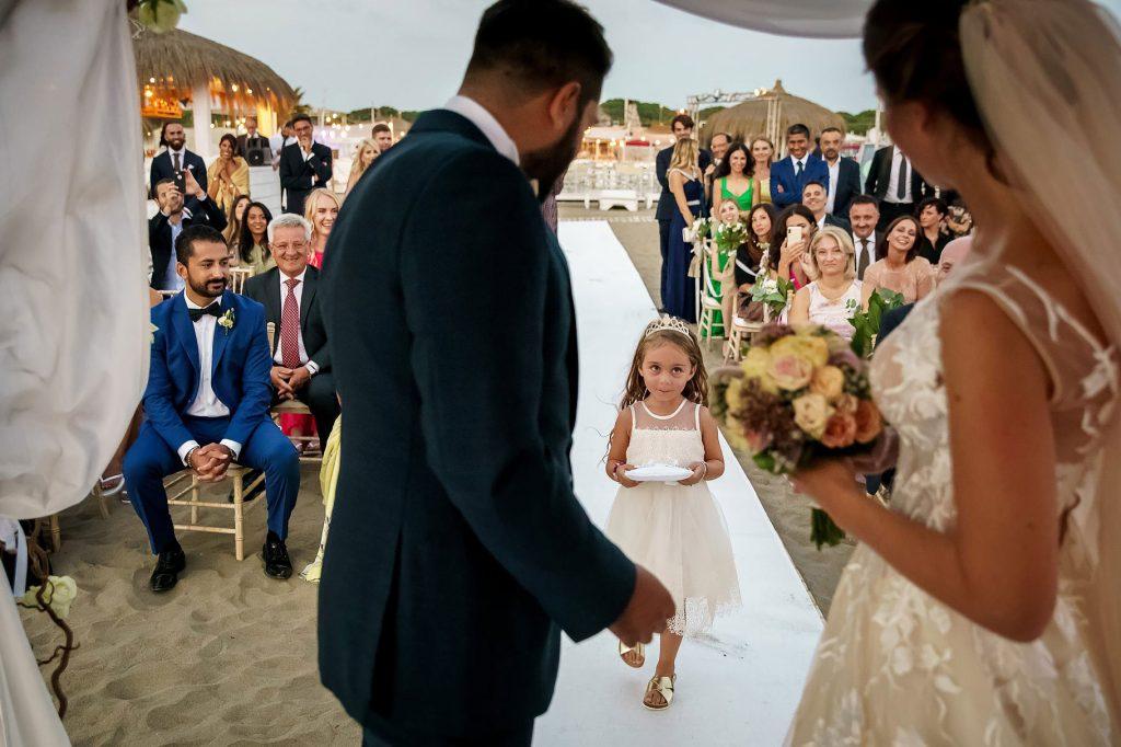 damigella porta la fedi per il matrimonio in spiaggia