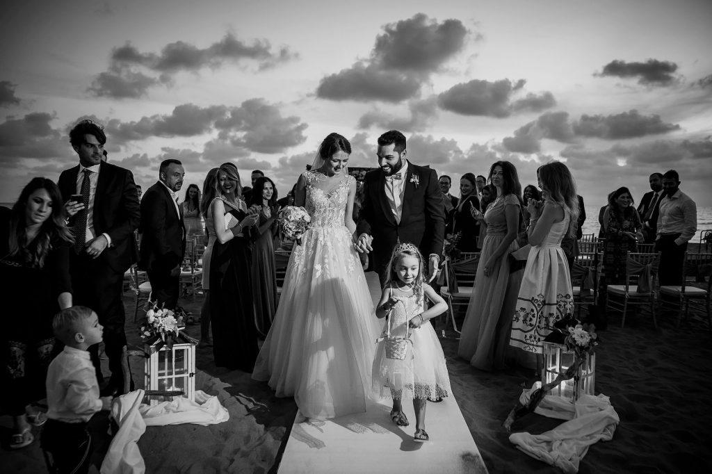 gli sposi escono dalla cerimonia dopo il matrimonio in spiaggia