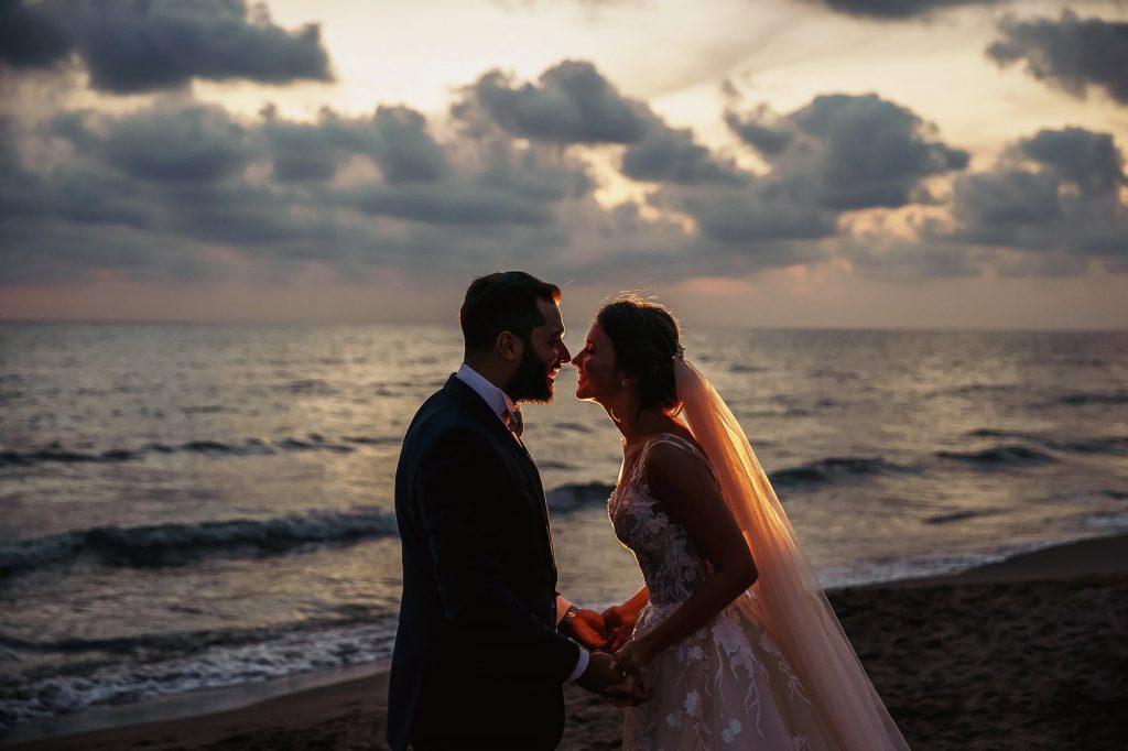 ritratto degli sposi in spiaggia dopo la cerimonia al tramonto