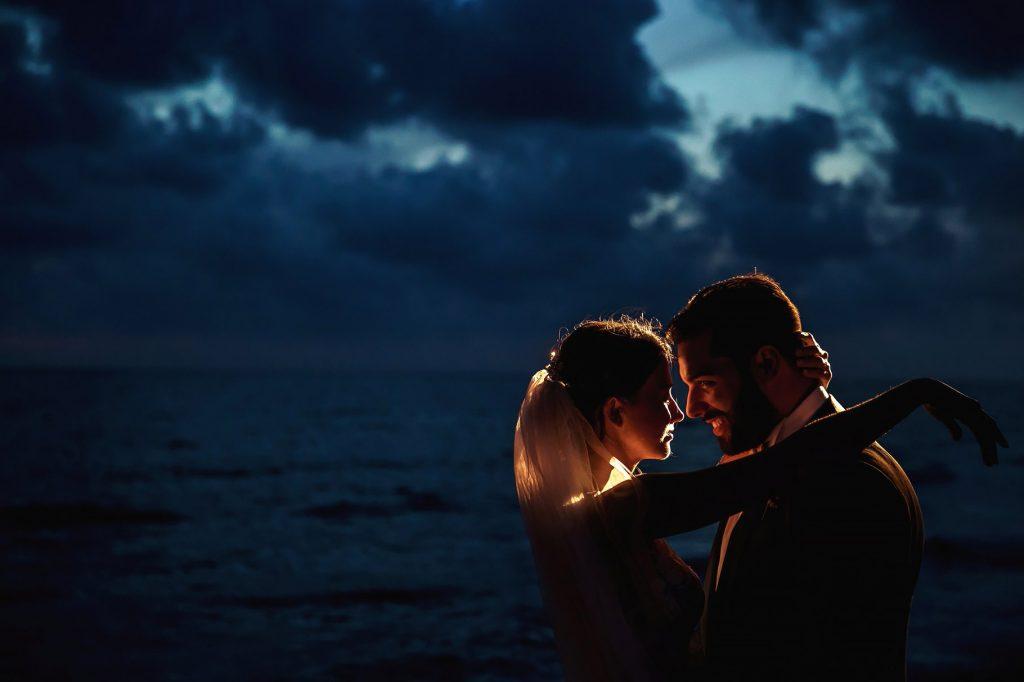 la sposa e lo sposo in spiaggia dopo la cerimonia al tramonto