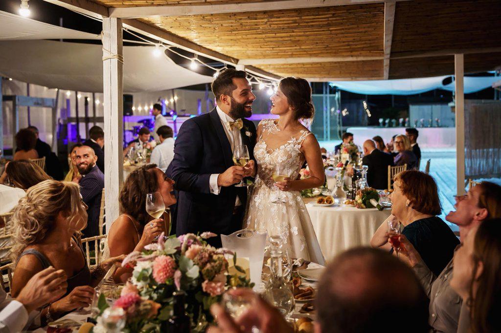 gli sposi salutano gli invitati al matrimonio in spiaggia