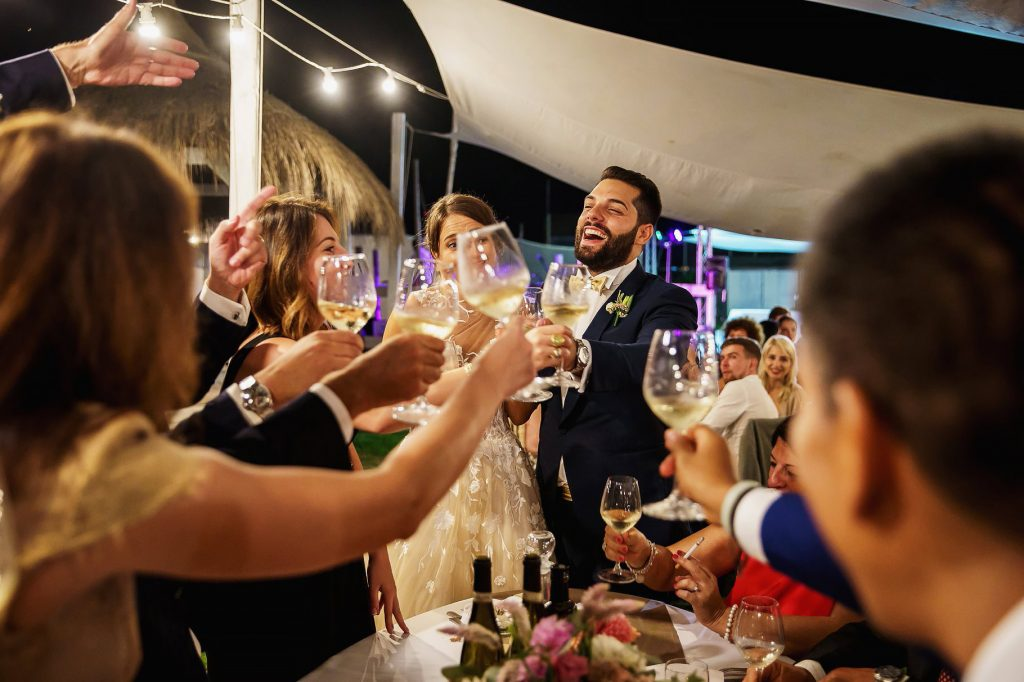 gli sposi brindano con gli invitati al matrimonio in spiaggia