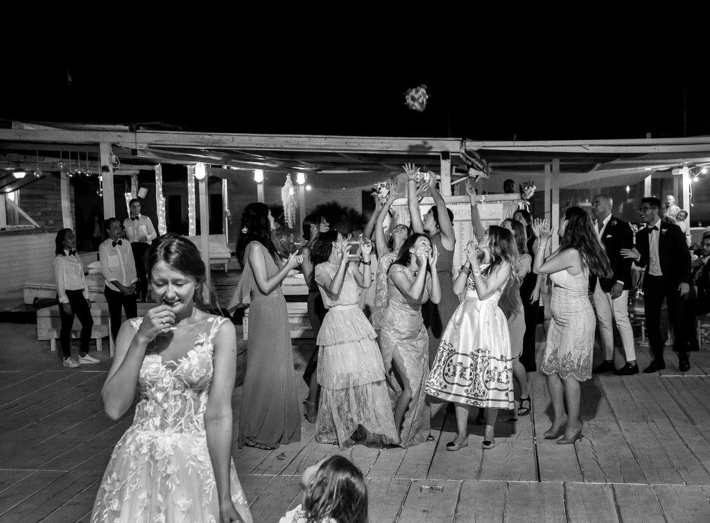 la sposa lancia il bouquet dopo il matrimonio in spiaggia