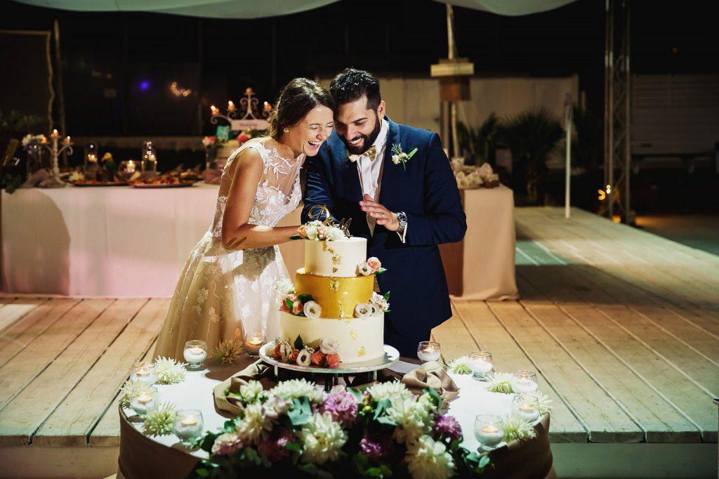 gli sposi e il taglio della torta di matrimonio in spiaggia