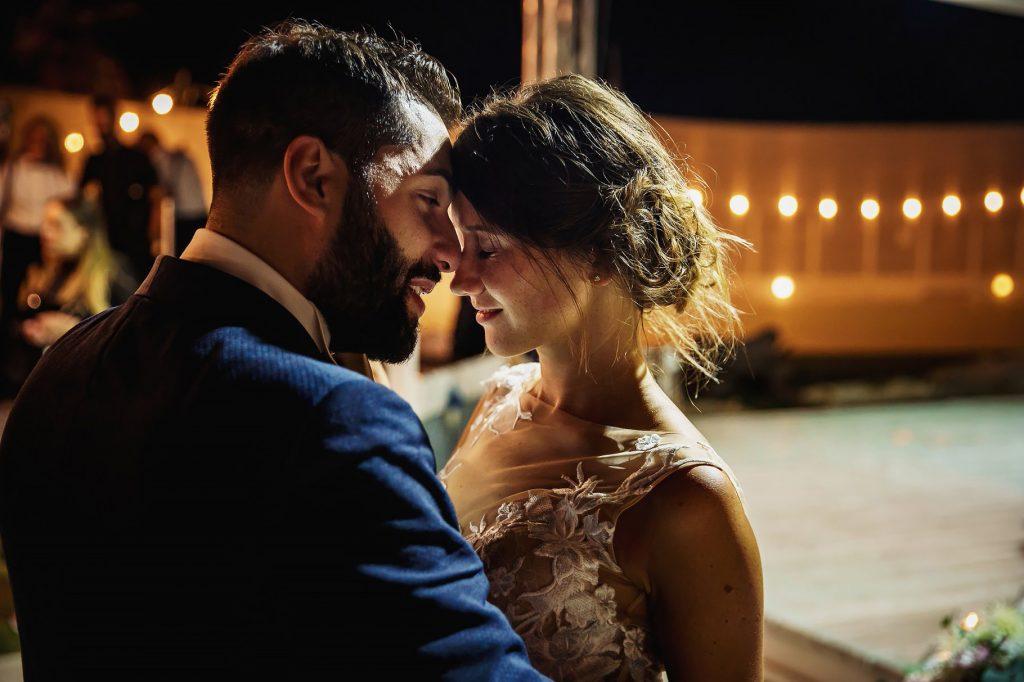 gli sposi guancia a guancia al termine del matrimonio in spiaggia