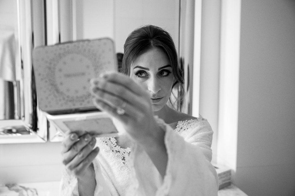 la sposa controlla il trucco allo specchio