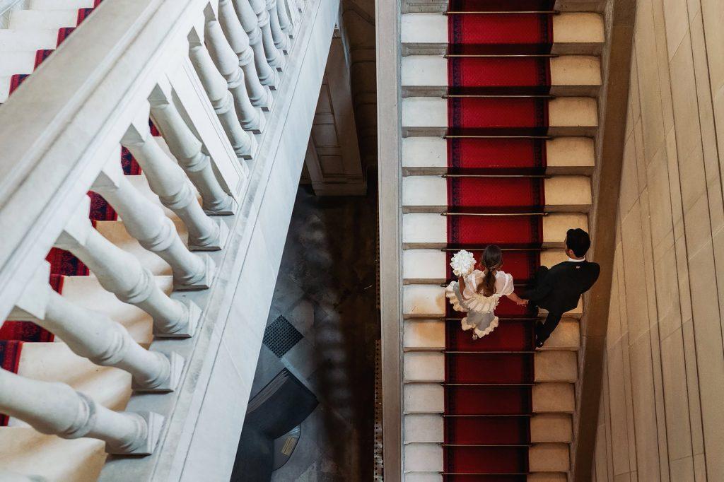 gli sposi salgono la scalinata del comune per il matrimonio a parigi