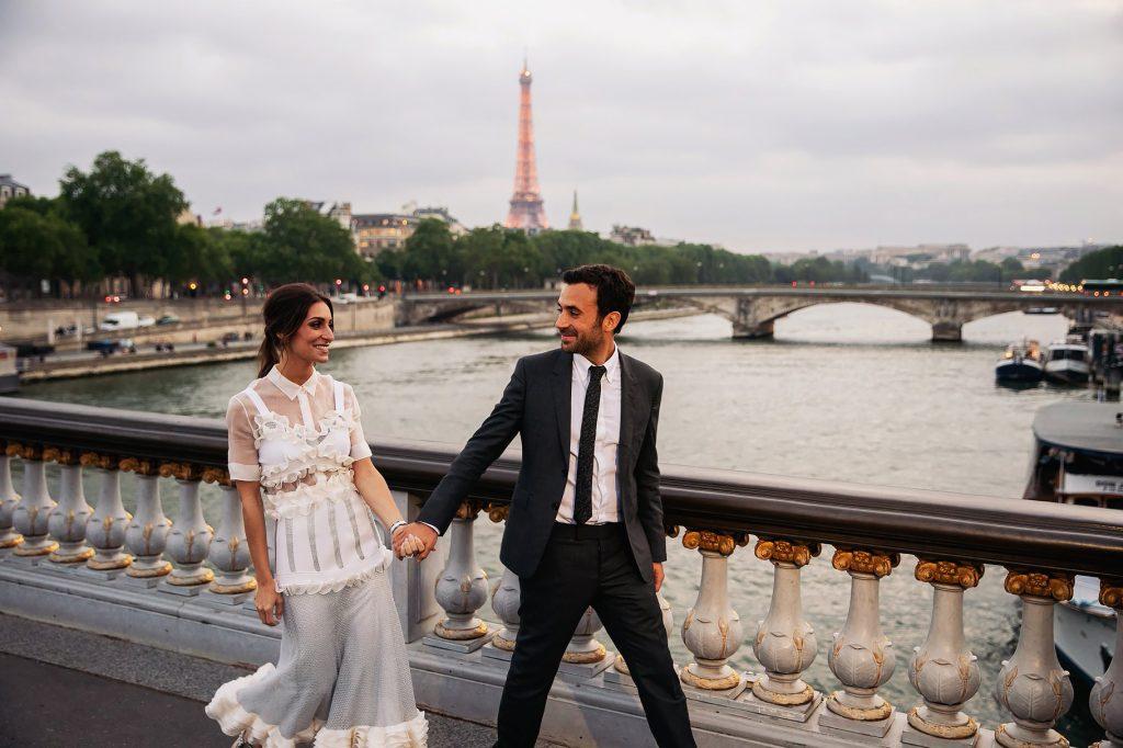 sposi che camminano mano nella mano su un ponte a parigi