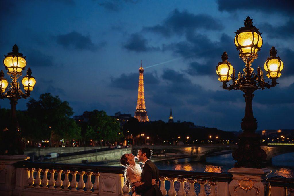 gli sposi abbracciati con la tour eiffel sullo sfondo al tramonto