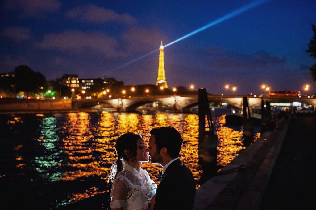 ritratto di coppia sposi di notte con la tour eiffel e la senna sulla sfondo