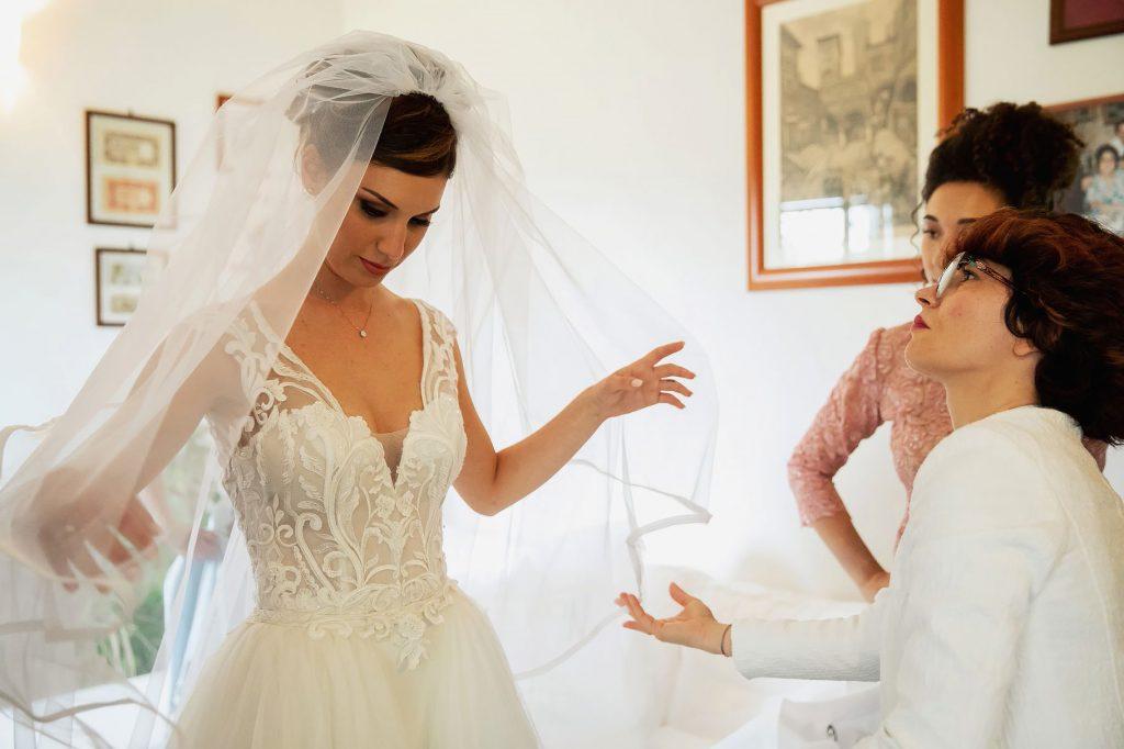 Sposa che indossa il velo nuziale per il matirmonio di lorenzo pellegrini