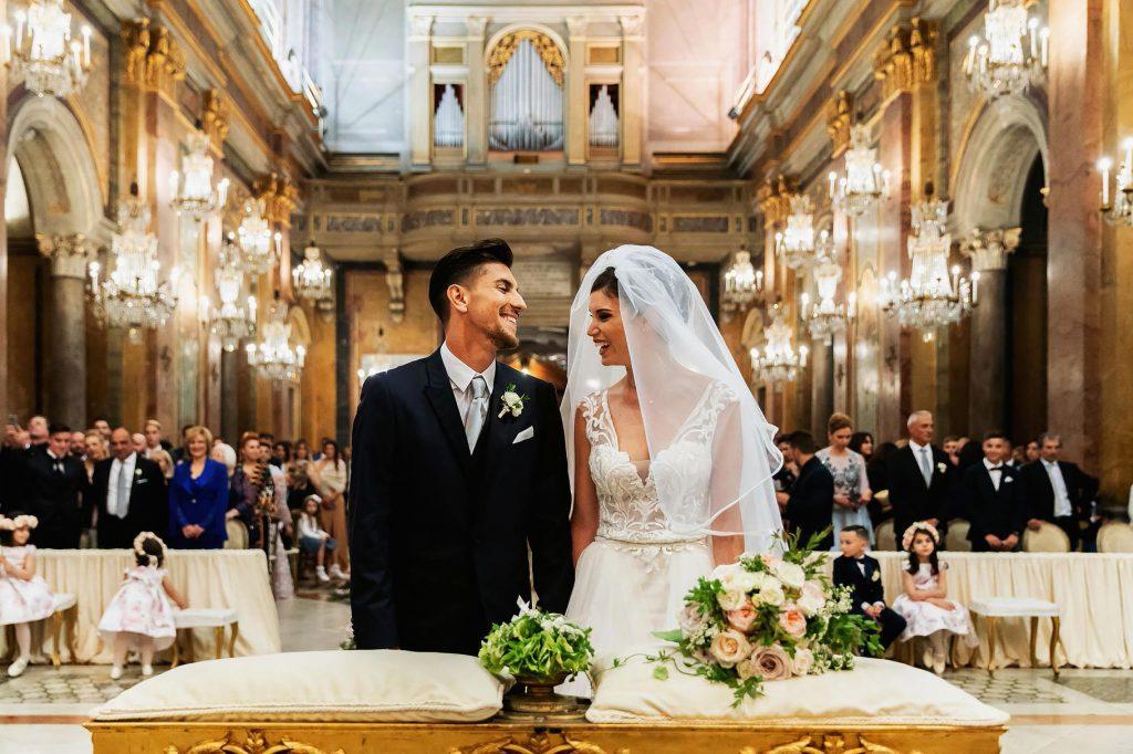 gli sposi felici e innamorati si guardano in chiesa