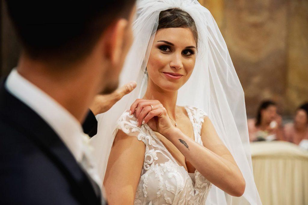 lo sposo aggiusta il velo alla sposa mentre lei lo guarda dolcemente in chiesa