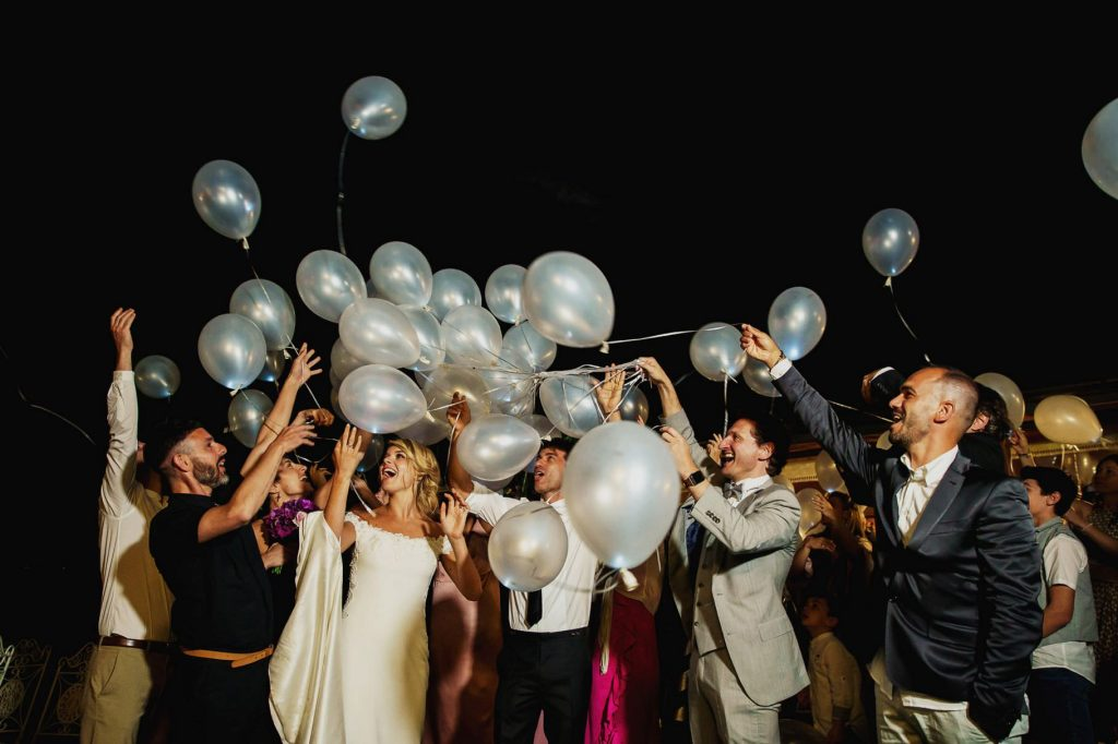 gli sposi e gli invitati lanciano i palloncini luminosi