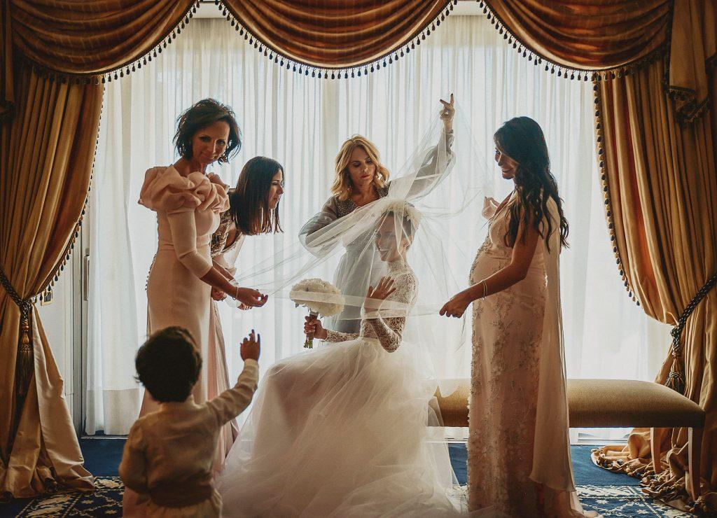 sposa che indossa il velo aiutata dalle damigelle in un elegante camera d'albergo