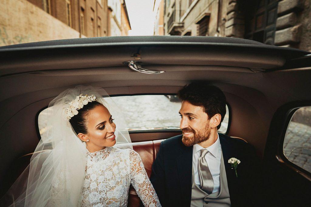 gli sposi felici in auto dopo il matrimonio italo-spagnolo