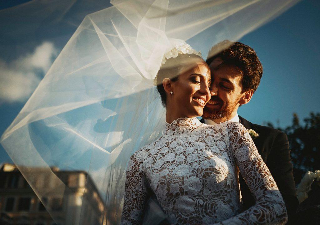 foto di coppia sposi sul ponte dellÕangelo con velo sollevato dal vento
