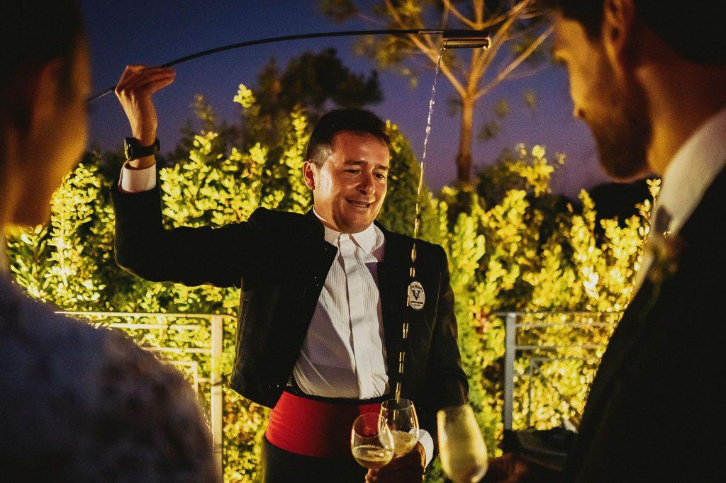 gli sposi guardano il sommelier e la mescita di vino coreografica durante il ricevimento del matrimonio italo-spagnolo