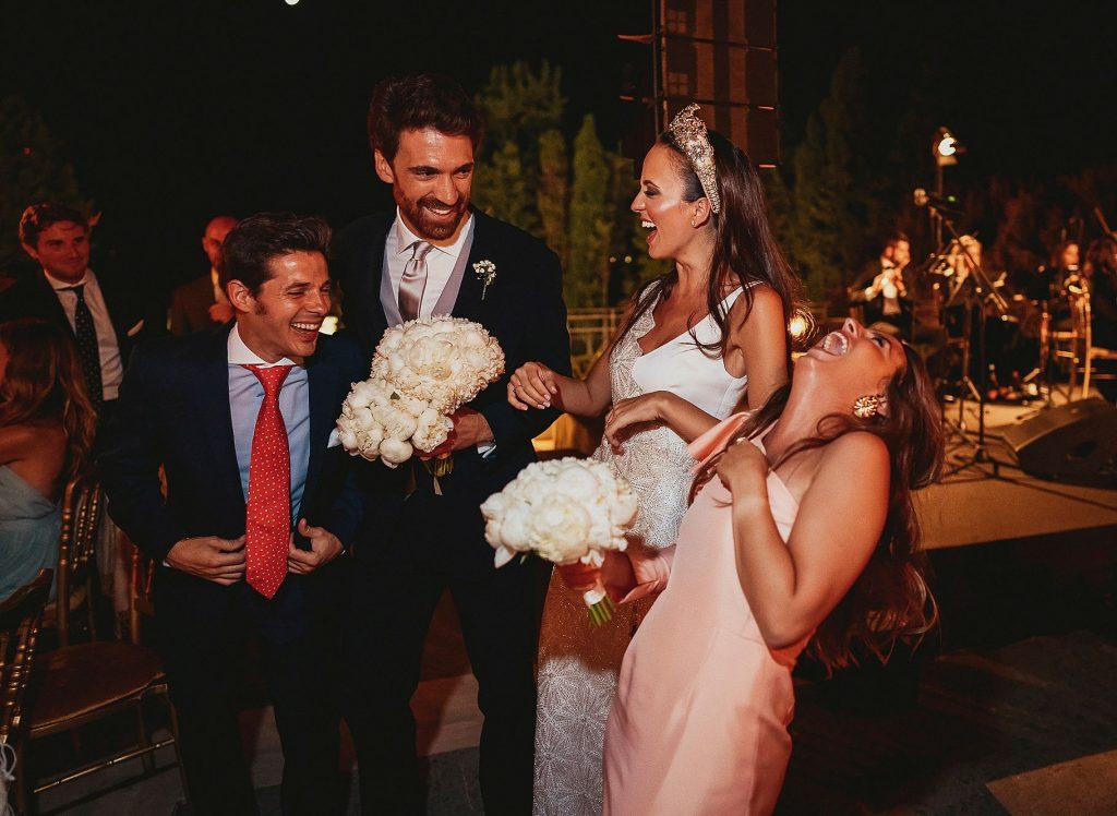 gli sposi ridono e scherzano con gli invitati al ricevimento di  matrimonio