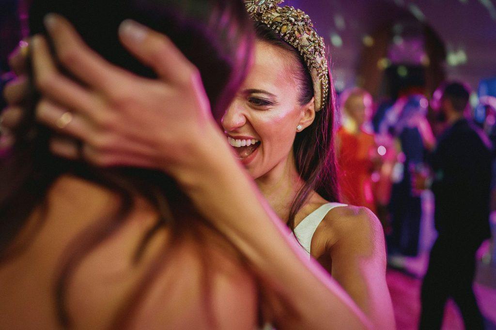 la sposa raggiante abbraccia un amica durante la festa danzante al matrimonio italo-spagnolo a villa miani