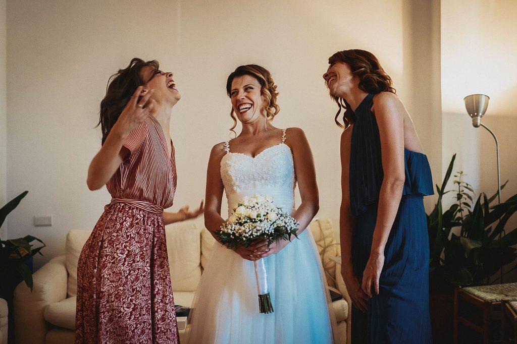 la sposa e le sorelle si divertono mentre posa per una foto di famiglia prima di uscire per andare al matrimonio a il conventino